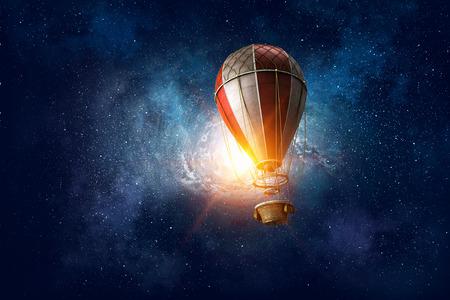 Color aerostat flying in dark starry sky Standard-Bild