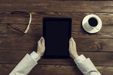 Top view of businesswoman sitting at table with tablet pc in hands
