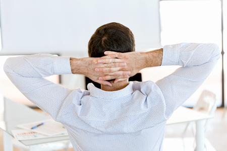 Rear view of sitting businessman with crossed hands on the head