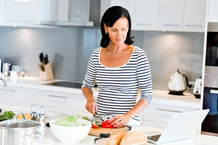 Beautiful woman standing in the kitchen and cooking