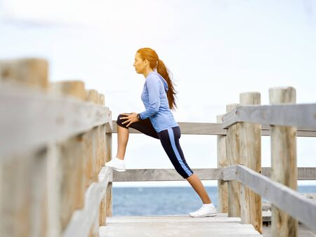 Young woman at the beach doing exercises Stockfoto