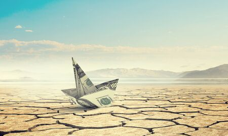 Dollar banknote ship in desert as symbol for financial crisis . Mixed media Stock Photo