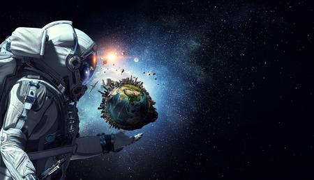 Astronaut holding Earth planet in palm. Standard-Bild