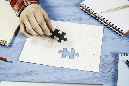 Hand of man completing puzzle with missing piece