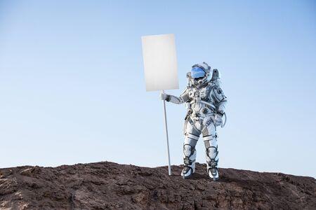 Astronaute tenant une bannière vierge pour la publicité. Technique mixte