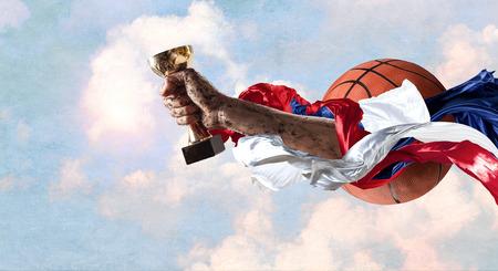 勝者の手は青空の背景に対してカップを締める