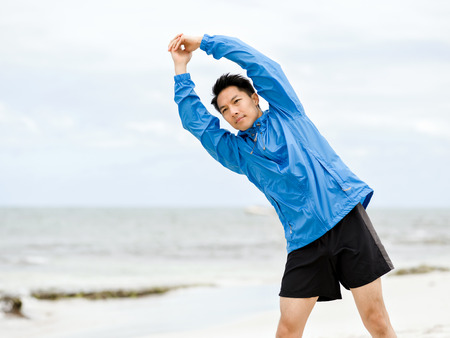 Young man doing exercise at the beach