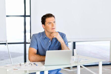 Pensive businessman at office Imagens