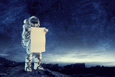 Astronaut on dark background holding white blank board. Mixed media