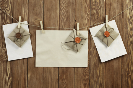 Envelopes hanging on rope on wooden background
