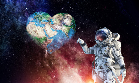 Astronaut touching with finger planet. Imagens