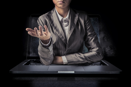 Businesswoman coming out of laptop screen with reached hand. Mixed media Zdjęcie Seryjne