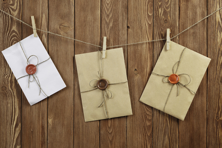 Envelopes hanging on rope on wooden background