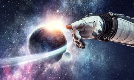 Close of astronaut robotic hand touching planet. Elements of this image furnished by NASA Stock Photo