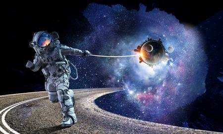 ロープで惑星を引っ張る宇宙空間の宇宙飛行士。この画像の要素は、NASAによって供給されています 写真素材