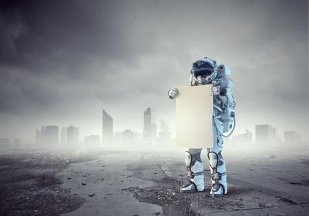 Astronaute dans l'espace tenant un tableau blanc blanc. Technique mixte
