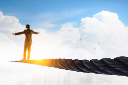 Homme d'affaires avec un bandeau sur les yeux marchant sur une corde haute dans le ciel