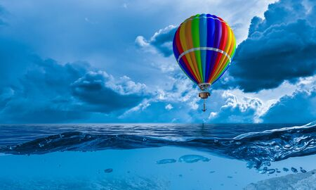 Aérostat de couleur vole au-dessus de la mer comme concept de liberté et de voyage