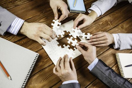 Group of business people sitting at table and assembling jigsaw puzzle Banque d'images