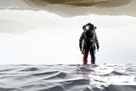 Astronaute en costume spatial, debout dans l'eau. Technique mixte Banque d'images