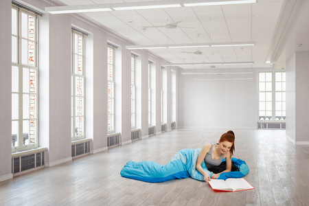 Young woman in sleeping bag in interior. Mixed media Banque d'images