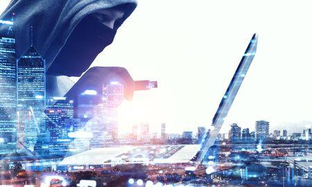 Double exposition de l'homme de pirate travaillant sur ordinateur portable et paysage urbain sur fond blanc Banque d'images