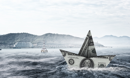 Ship made of dollar banknote floating in water . Mixed media