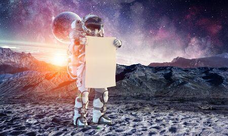 Astronaute dans l'espace tenant un tableau blanc blanc