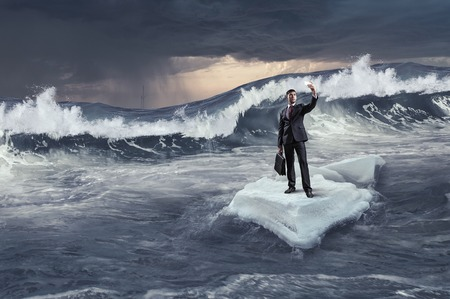 Businessman on ice block floating in sea and making selfie. Mixed media