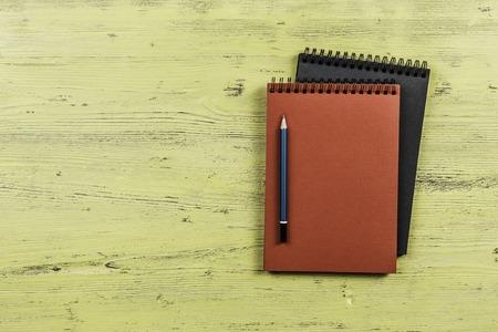 Vue de dessus de deux bloc-notes avec un crayon sur fond en bois