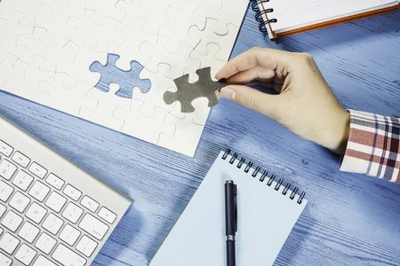 Main de femme complétant le puzzle avec pièce manquante Banque d'images