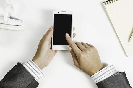 Vue de dessus de la main de femme d'affaires avec smartphone sur tableau blanc