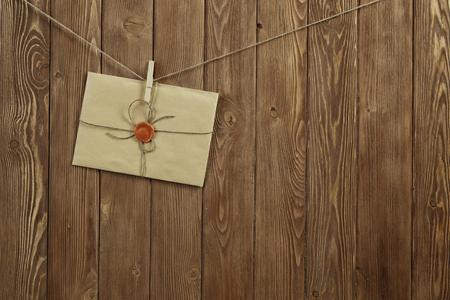 Enveloppe suspendue à la corde sur fond de bois