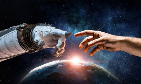 Astronauts hands in touch as symbol for creation.