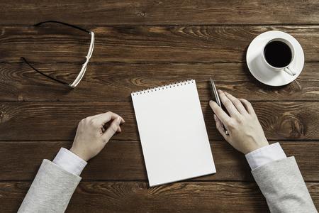 Vue de dessus de la femme d'affaires à table avec le bloc-notes et un stylo Banque d'images