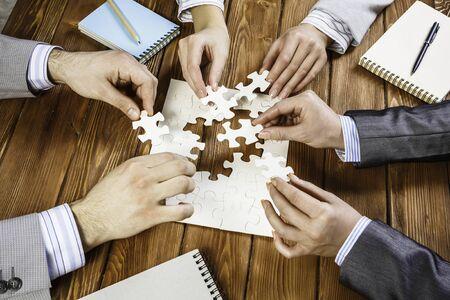 Groupe de gens d'affaires assis à table et assemblage de puzzle