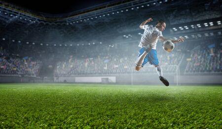 Arène sportive et joueur de football frappant la balle. Technique mixte