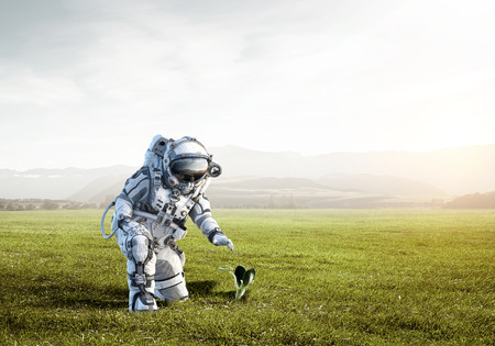 Astronaut on field and green growing sprout. Mixed media