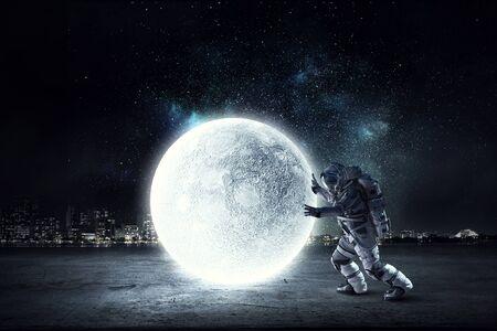 Astronaut in der Klage, die Planetenrolle bildet. Gemischte Medien Standard-Bild