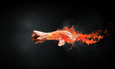Close of male fist in fire flames