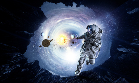 Astronaut in outer space pulling planet on rope. Elements of this image are furnished by NASA