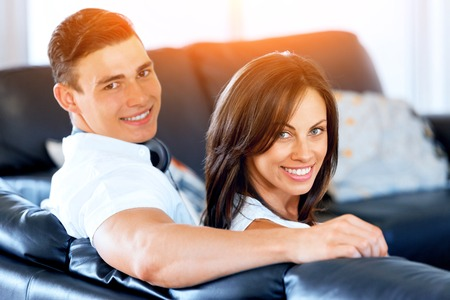 Young couple looking at camera while sitting at home