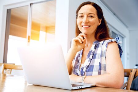 Mature beautiful woman working on her laptop Stock Photo