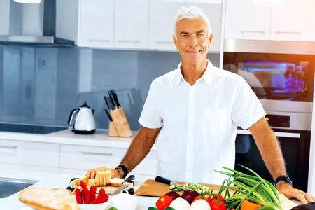 Portrait of a smart senior man standing in kitchen