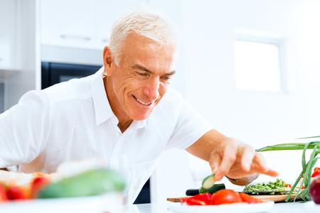 Portrait of a smart senior man cooking in kitchen Reklamní fotografie