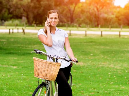 公園で自転車を持つ美しい若いブロンドの女性