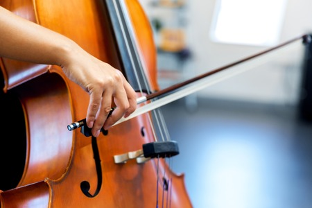 Close up of cello with bow in hands Stock Photo