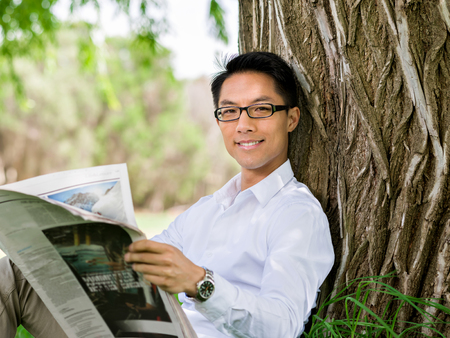 Business man reading a newspaper in park Stock Photo