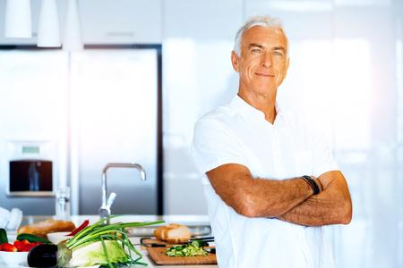 Portret van een slimme hogere mens die zich in keuken bevindt