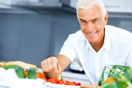 Portrait of a smart senior man cooking in kitchen Stockfoto